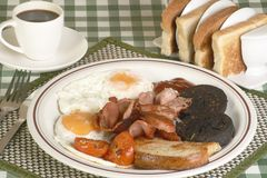 Cooked breakfast. Full english breakfast of bacon egg tomato black pudding and fried bread on a gingham cloth Royalty Free Stock Photo