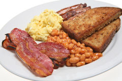 Cooked Breakfast. English fried breakfast with sausage, streaky bacon, fried bread, baked beans and scrambled egg Stock Photos
