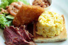 Cooked breakfast. Of crisply fried beef, scrambled eggs, toast bread, beans, triangle fried potato with salad Stock Image