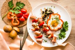 Cooked breakfast - scrambled eggs, sausage and peppers. Wooden table. Top view Royalty Free Stock Image