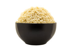 Cooked brown rice isolated on white background. Cooked brown rice in black bowl isolated on white background Royalty Free Stock Photo