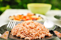 Cooked brown rice in plate with spoon and fork Stock Photos