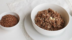 Cooked buckwheat groats with butter and mug of milk on a table stock video
