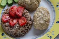 Cooked buckwheat and meatballs on the plate decorated by tomato and cucumber. Cooked buckwheat and meatballs on plate decorated by tomato and cucumber stock image
