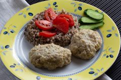 Cooked buckwheat and meatballs on the plate decorated by tomato and cucumber. Cooked buckwheat and meatballs on plate decorated by tomato and cucumber royalty free stock photo