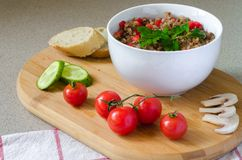 Cooked buckwheat porridge with chopped sweet red pepper. And branch of parsley on top in a white bowl, sliced bruschetta, cucumbers, cherry tomatoes and Stock Photo