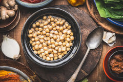 Cooked chick peas in dish with spoon and cooking ingredients on rustic wooden kitchen table background, top view. Healthy vegetar Stock Images