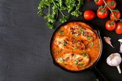 Cooked chicken breast, top view. Cooked chicken breast with tomato sauce in frying pan on dark stone background with copy space, top view Royalty Free Stock Image