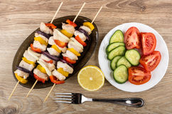Cooked chicken shashlik in brown dish, plate with cucumbers, tom Royalty Free Stock Image