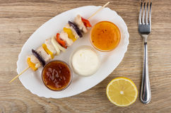 Cooked chicken shashlik with sauces in dish, fork and lemon Royalty Free Stock Photography