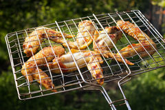 Cooked chicken wings on the grill, brazier, on background of grass. Selective focus,  toned image, film effect. Cooked chicken wings on the grill (brazier), on Stock Images