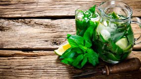 Cooked cocktail of lime, mint, rum and ice on wooden table . Top view Royalty Free Stock Images