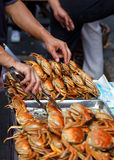 Cooked crab street food. A man prepares a tray of freshly cooked crabs on the street ready for eating Stock Image