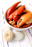 Cooked crabs, food. A photograph of a dish of freshly cooked crab legs in a white bowl on a striped table cloth. Vertical color image, nobody in picture. Simple stock photography