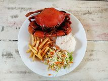 Cooked crabs on white plate served with salad and french fries, Stock Photo