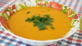 Cooked and decorated with greens pumpkin cream soup in a plate. Healthy food stock footage