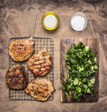 Cooked, delicious grilled pork steak with green salad of cucumber, spinach and arugula wooden rustic background top view close Royalty Free Stock Image