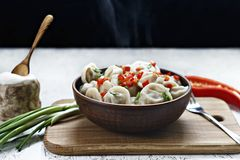 Cooked dumplings in a clay dish with pepper and onions. stock photos