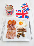 Cooked english breakfast with british flag and tea. Full fried english breakfast on a square white plate on a rustic white table top with knife and fork and Stock Photo