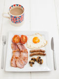 Cooked english breakfast with cup of tea Royalty Free Stock Photos