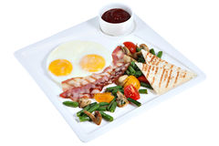 Cooked English breakfast, fried eggs with bacon on square platte royalty free stock images