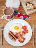 Cooked english breakfast on a wooden table. English breakfast on a wooden table with butter dish, cup of tea,  toast and British flag Stock Photos