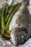 Cooked fish dorada with asparagus on the foil Stock Image