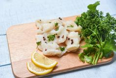 Cooked fish fillet piece with lemon and spices on wooden cutting board background - pangasius dolly fish meat royalty free stock photo