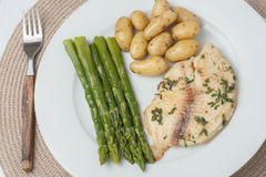 Cooked fish with parsley servied with asparagus Royalty Free Stock Image