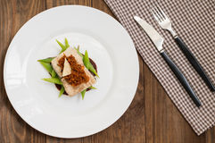 Cooked fish with steamed asparagus, vegetable ragout, tomato sauce and potato chips. Wooden background. Top view. Close Royalty Free Stock Photos