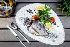 Cooked fish on white plate in restaurant at wooden table Stock Photos