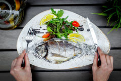Cooked fish on white plate in restaurant at wooden table Royalty Free Stock Images