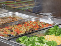 Cooked food on hot tray. Hot trays with cooked food close-up in dining room royalty free stock images