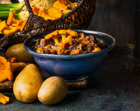 Cooked forest Mushrooms in rustic bowl and potato on dark rustic background, front view. Autumn cooking stock photo