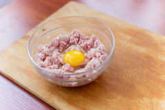 Cooked fresh mince for dish with raw egg lie in a plate Stock Photo
