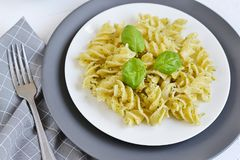Cooked fusilli pasta on a plate with pesto. Italy food, healthy concept, vegetarian royalty free stock images