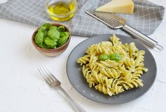 Cooked fusilli pasta on a plate with pesto. Italy food, healthy concept, vegetarian royalty free stock image