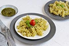 Cooked fusilli pasta on a plate with pesto. Italy food, healthy concept, vegetarian stock images