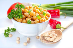 Cooked garbanzo beans. Cooked garbanzo beans (chick peas) in a bowl served with raw vegetables stock images