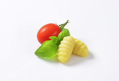 Cooked gnocchi. With cherry tomato and fresh basil on white background royalty free stock photos