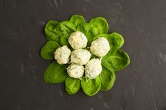 Cooked gnocchi over green fresh spinach leaves with cheese, Flat. Cooked gnocchi over green fresh spinach leaves with cheese on grey background, Flat lay stock image