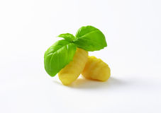 Cooked gnocchi. Two cooked gnocchi with fresh basil on white background stock image