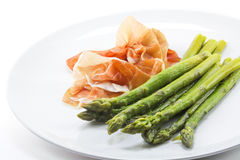 Cooked green asparagus and raw ham on a plate, white background,. Closeup shot with selected focus and narrow depth of field Royalty Free Stock Images
