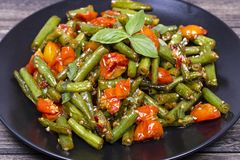 Cooked green beans, red cherry tomato with sesame seeds in black plate. Close up Stock Photos