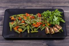 Cooked green beans, red cherry tomato with sesame seeds in black plate. Close up Stock Image