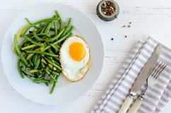 Cooked green beans with fried egg Stock Photography