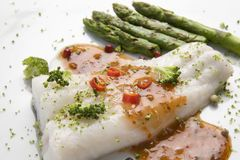 Cooked hake dinner. An delicious hake cooked with sauce,red peppers and asparagus sideway Royalty Free Stock Photography