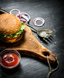 Cooked hamburger with ketchup and onion rings Stock Image