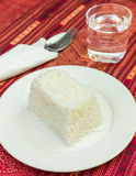 Cooked jasmine rice on white dish with spoon, fork, glass of wat Royalty Free Stock Photos