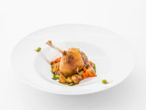 Cooked leg of poultry with garnish. On white plate Stock Image